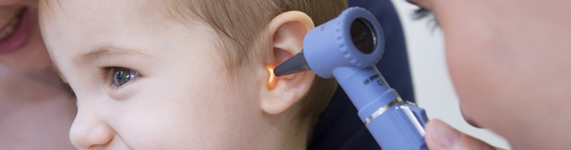 Child getting their ear checked with a medical tool