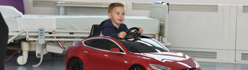 Paediatric patient driving a mini-tesla used to drive them to and from surgery