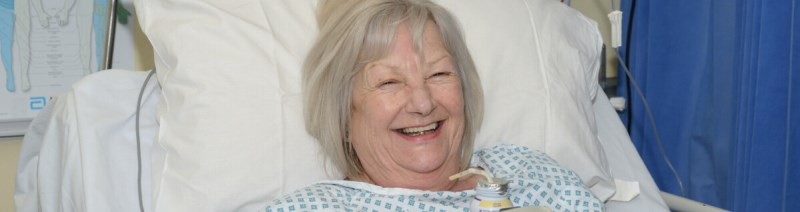 A patient in a hospital bed smiling