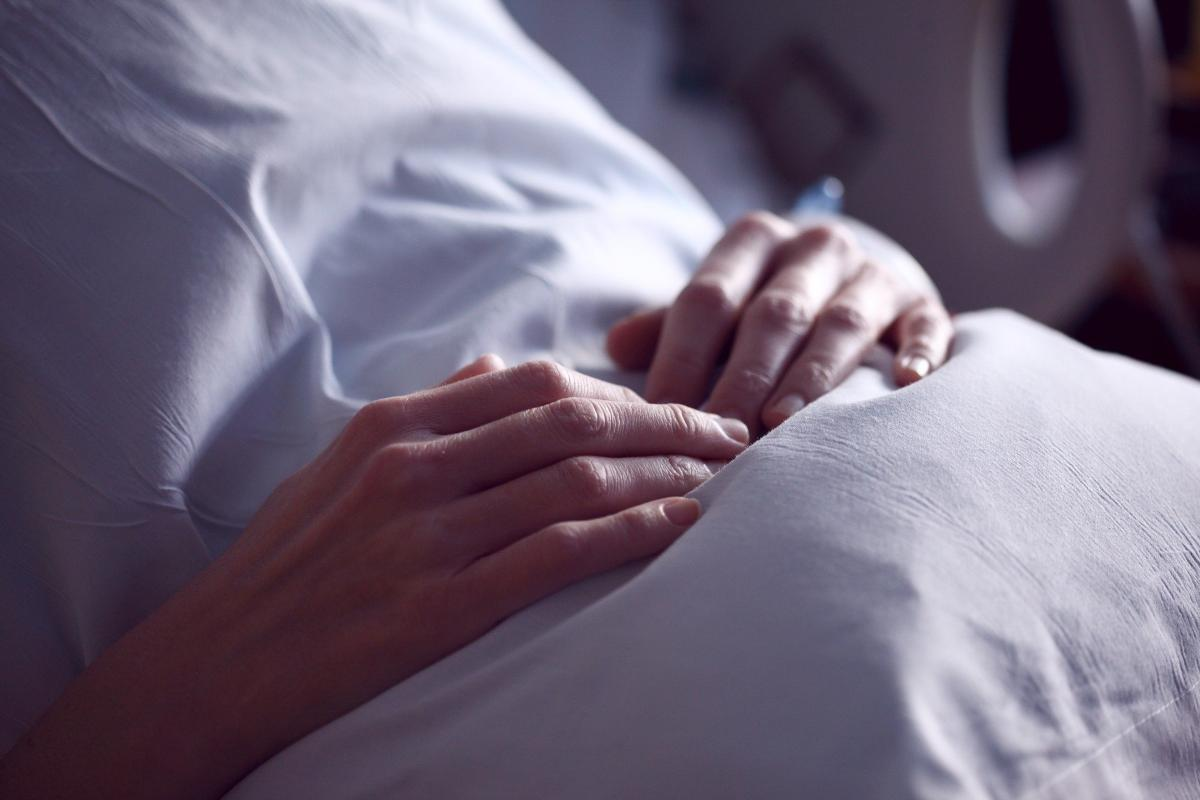 Hands of a female patient holding a pillow against her stomach