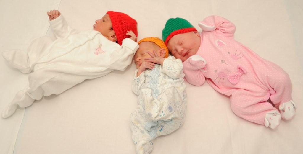 Three sleeping babies wearing knitted hats