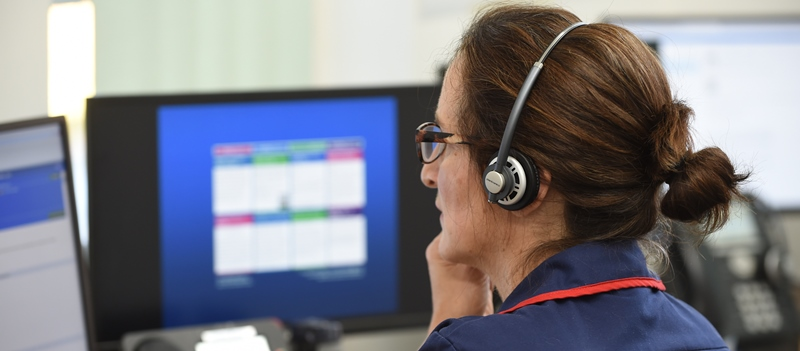 Staff member, woman, in unfiorm and wearing a headset, working at her computer.