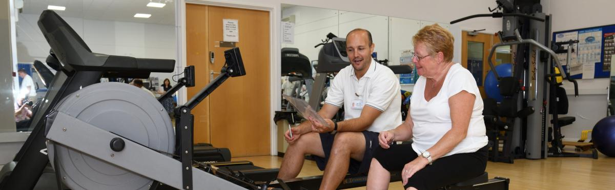 A physiotherapist, in uniform, working with a patient in the Prehab Gym