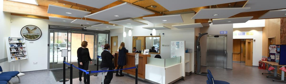 Pic of the inside of a GP waiting areas. Reception desk in the background with people queuing