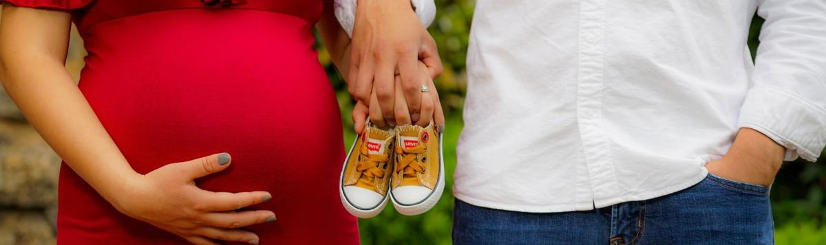 Pregnant woman and male partner holding baby shoes