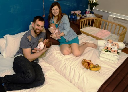 Man and woman on hospital beds holding their babies