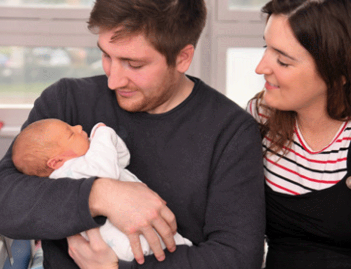 Parents looking down at newborn baby