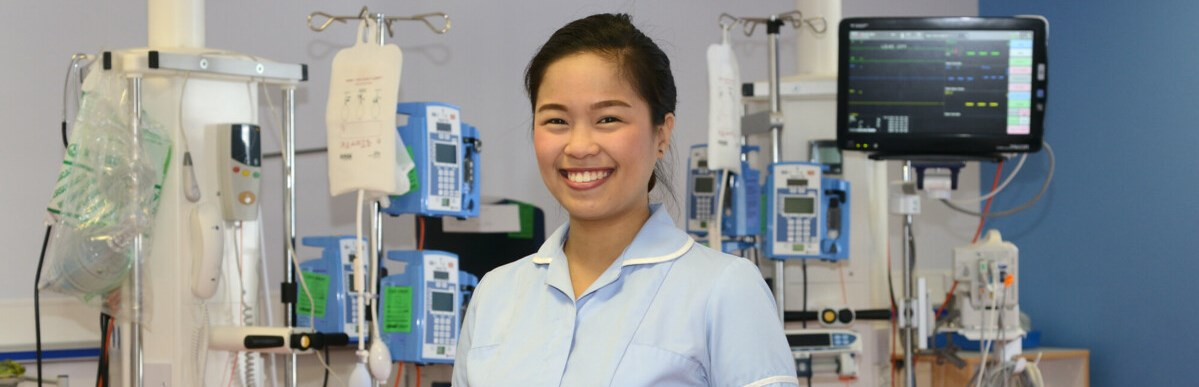 Nurse by equipment, smiling
