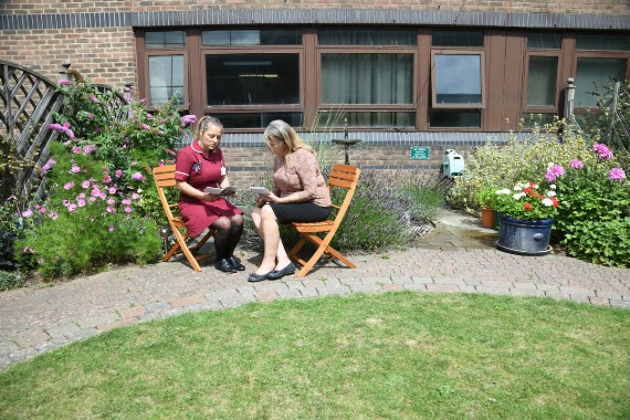Chief nurse talking with another staff member, sitting on wooden chairs in a garden area
