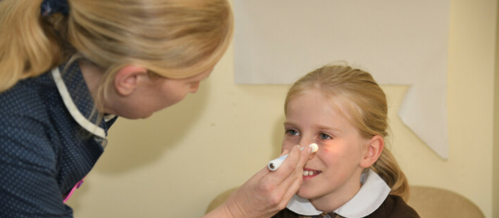 Specialist nurse shining a light into a child patient's eyes