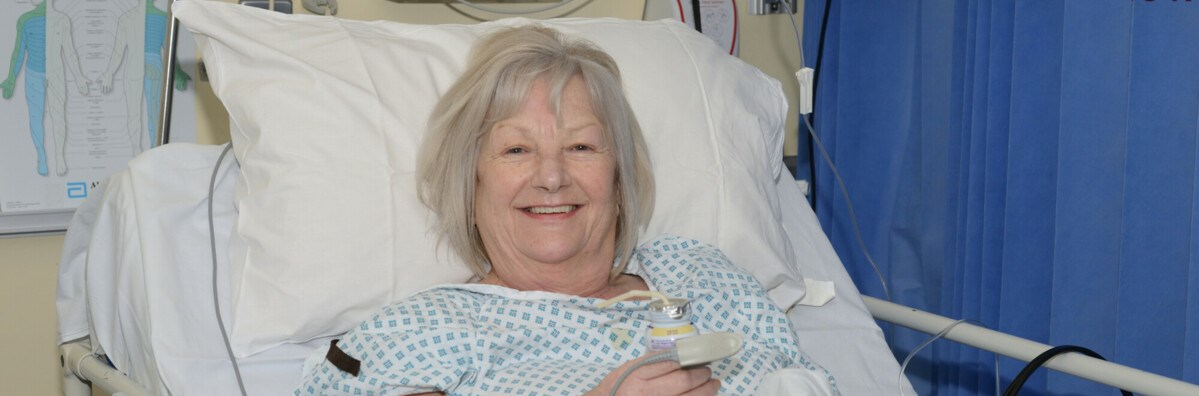 Patient in a hospital gown and in bed, smiling