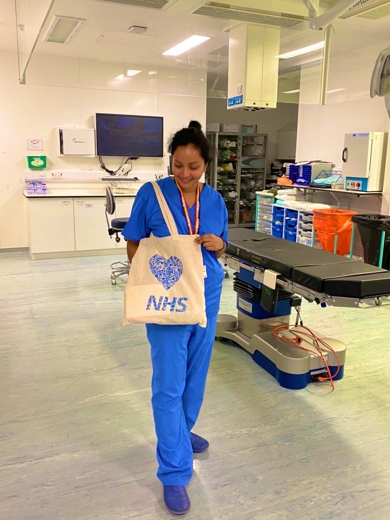 Staff member in scrubs posing with a wellbeing bag