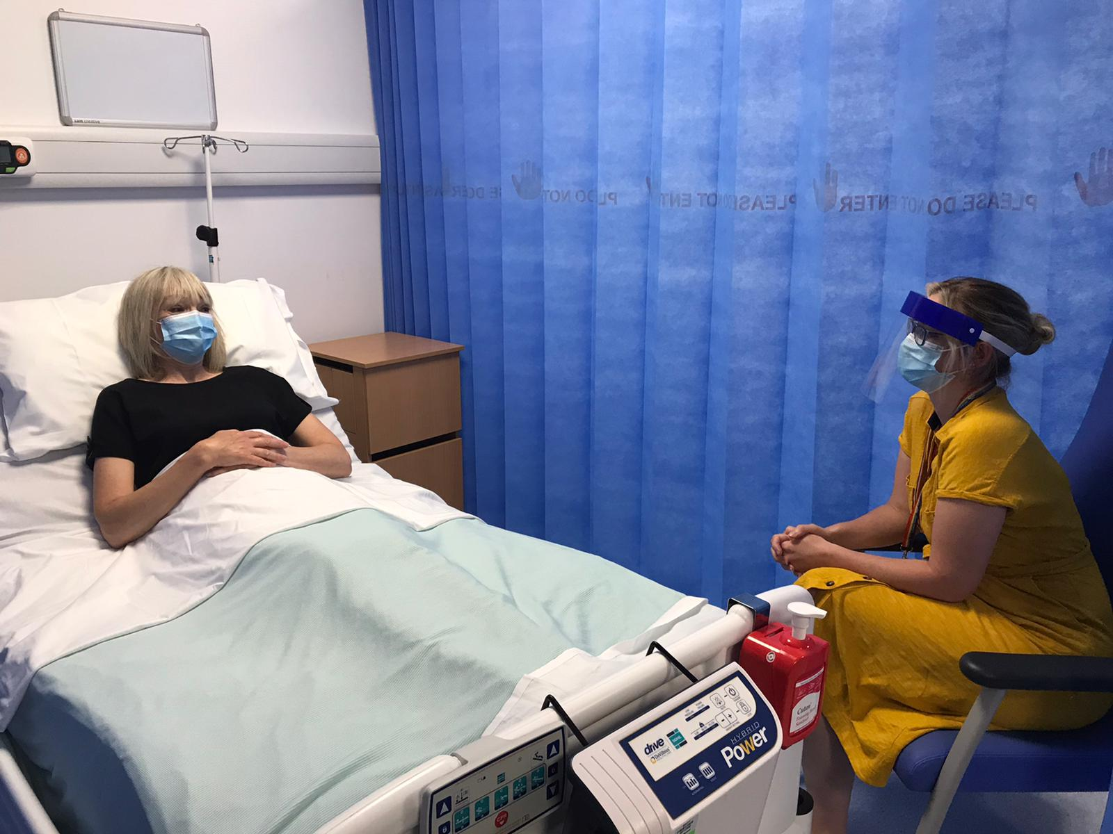 Pic of a patient in bed with a visitor. Both wearing surgical masks/relevant PPE.