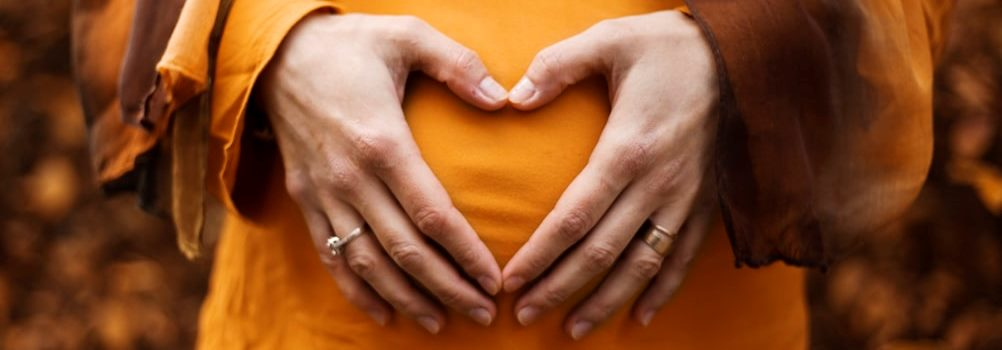 Pregnant woman with ther hands forming a heart over her baby bump