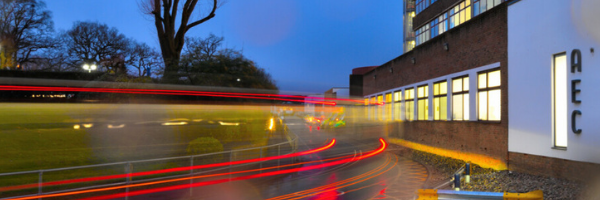 Pic of the outside of the hospital at night. A red blurred effect across the road of cars/ambulances driving past.